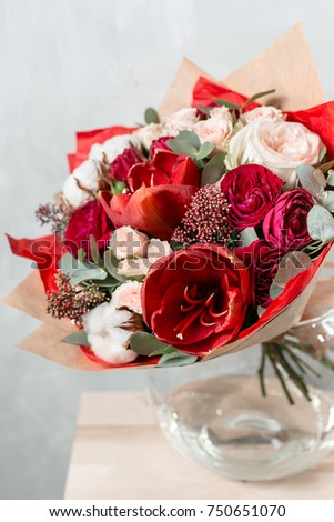 beautiful bouquet of mixed flowers into a vase on wooden table #750651070