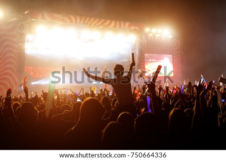 Slhouette of young man on concert, big festival event Royalty-Free Stock Photo #750664336