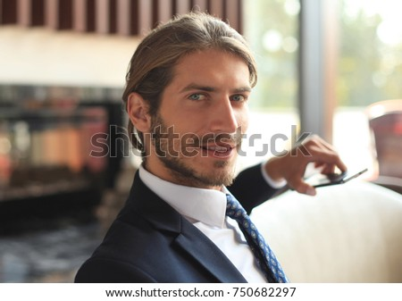 Portrait of happy young businessman sitting on sofa in hotel lobby. #750682297