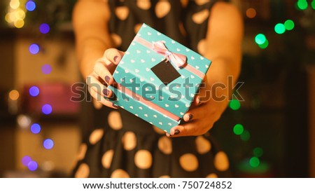 A girl in an evening dress gives a New Year gift #750724852