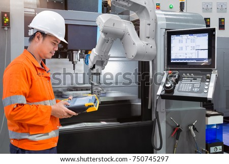 Maintenance engineer programming automatic robotic hand with CNC machine in smart factory. Industry 4.0 concept #750745297