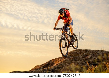 Cyclist in Red T-Shirt Riding the Bike Down the Rock on the Sunset Sky Background. Extreme Sport and Enduro Biking Concept. #750769342