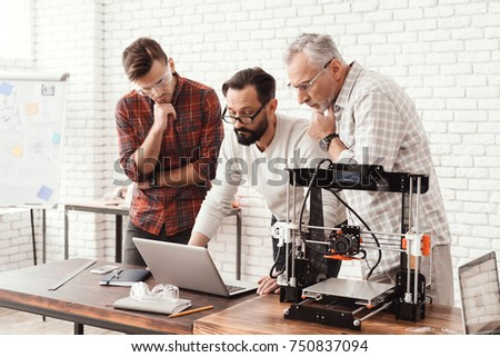 Three men are working on preparing a 3d printer for printing. One of them explains the rest of the subtlety to the print. A young and elderly man is looking at the laptop monitor screen. #750837094