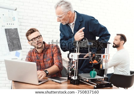 Three scientists are involved in setting up and developing 3D printers. An elderly man in a dark robe controls the work of his team. They are in the modern laboratory. #750837160