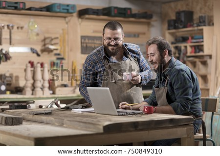 Two wood designer working with laptop in workshop. #750849310