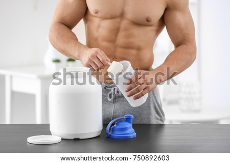 Young sporty man preparing protein shake at table #750892603