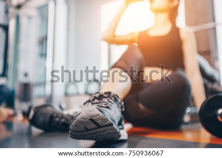 Asian woman exercising in the gym, Young woman workout in fitness for her healthy and office girl lifestyle. #750936067