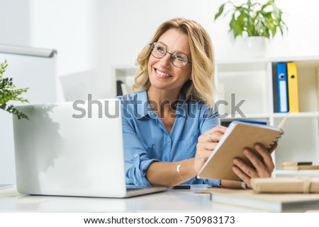 beautiful businesswoman writing in diary and using laptop at workplace in modern office #750983173