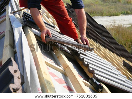 Roofing construction with clay roof tiles. Roofer laying ceramic roof tiles. Lay roof tiles. #751001605