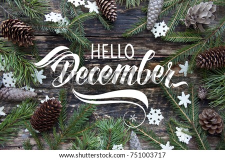 "Great season texture with winter mood. Spruce branches, cones and snowflakes on old wooden rustic background. Nature december background with hand lettering ""Hello December"". #751003717"