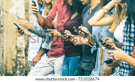 Group of multicultural friends using smartphone outdoors - People hands addicted by mobile smart phone - Technology concept with connected men and women - Shallow depth of field on vintage filter tone #751028674