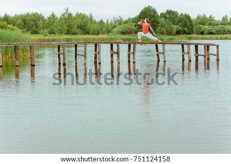 Man doin yoga with beer on pier at lake #751124158