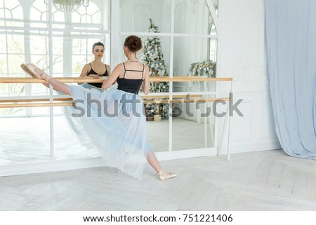 Young classical Ballet dancer side view. Beautiful graceful ballerine practice ballet positions in tutu skirt near large mirror in white light hall. Ballet class training #751221406