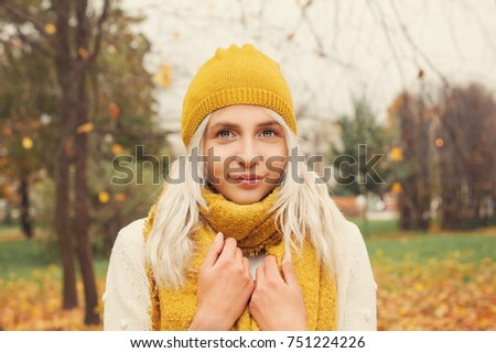 Cute Autumn Woman Fashion Model with Yellow Scarf and Hat in the Autumn Park Outdoors #751224226