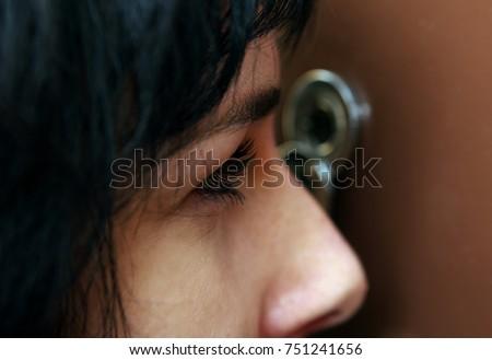 Closeup of woman looking through peephole #751241656