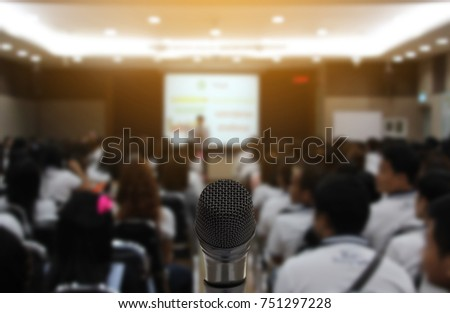 Microphone over the Abstract blurred photo of conference hall or seminar room with attendee background,Small Business training concept,Public speaking using as background and wallpaper. #751297228