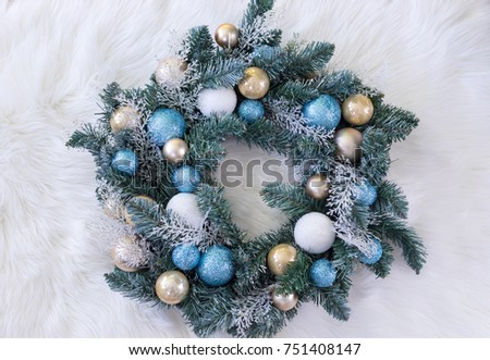 Christmas wreath with blue, white and beige ornaments on a white fuzzy background.  #751408147