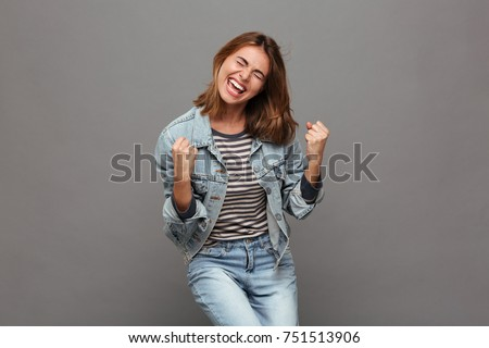 Portrait of a joyful happy teenage girl dressed in denim jacket celebrating success while dancing isolated over gray background Royalty-Free Stock Photo #751513906