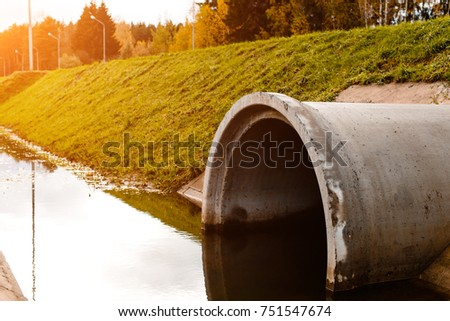 Concrete culvert pipe hole system draining sewage water in rays of the sun #751547674