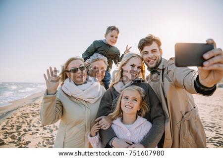 multigenerational family taking selfie on smartphone at seaside Royalty-Free Stock Photo #751607980
