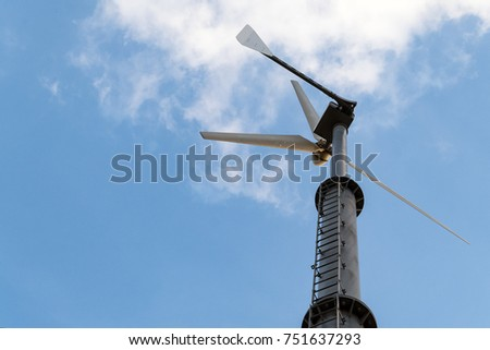Wind turbine generating electricity with a nice white cloud on the sky #751637293