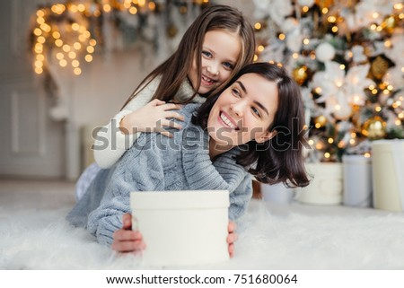 Happy female model with short dark hair and her adorable small girl have fun together, celebrate Christmas, exchange presents, have smiling expressions, have joy. Friendly family with presents