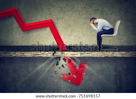 Depressed business man looking down at the falling red arrow going through a concrete floor. Fall and depreciation concept. #751698157