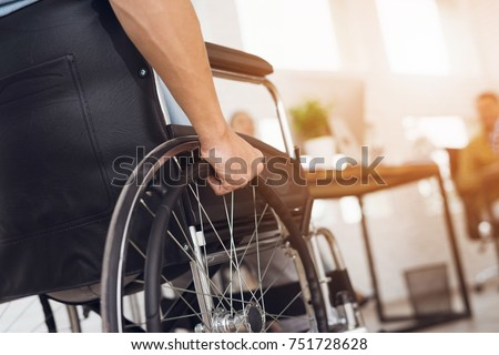 A disabled man is sitting in a wheelchair. He holds his hands on the wheel. Nearby are his colleagues Royalty-Free Stock Photo #751728628