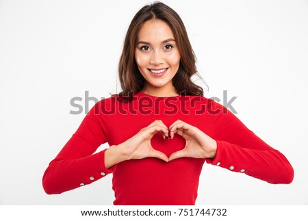 Portrait of a smiling young asian woman showing heart gesture with two hands and looking at camera isolated over white background #751744732