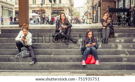 Group of girls sitting on the city stairs with smartphone. Technology isolation and emotional depression #751935751