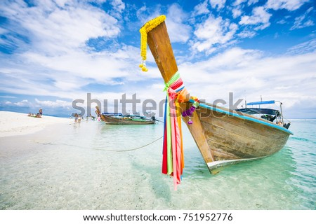 Traditional Thai wooden longtail boat with decorative sash ribbons moored in crystal waters on the shore of Bamboo Island near Krabi #751952776
