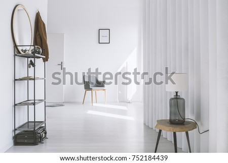 Lamp on wooden table in anteroom with mirror on shelf and chair against wall with picture next to door #752184439