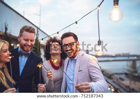 Four friends holding sparklers