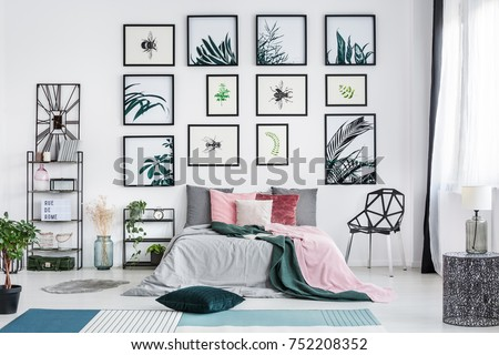 Designer chair next to bed with pink pillows in bright bedroom with posters and lamp on metal table #752208352