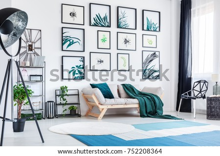 Blue and white carpet in designer living room with gallery above sofa with green blanket on chair #752208364