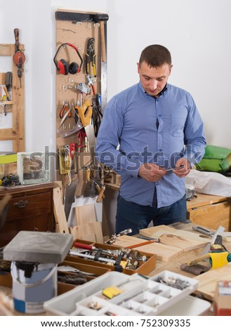positive european adult woodworker working  wood plank at workplace #752309335