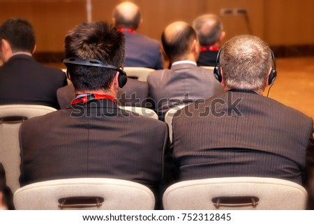 Unrecognizable people using in ear headphones for translation during event Unrecognizable business people using headphones for translation during event Royalty-Free Stock Photo #752312845