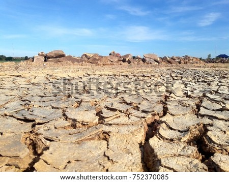 dry arid cracked ground with big rocks in blue sky white clouds #752370085