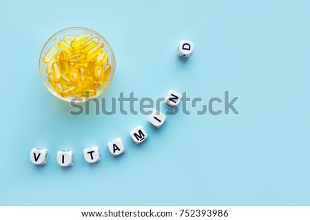 Yellow capsules in the round glass bowl and the word vitamin D from white cubes with letters on a blue background. VITAMIN D word for healthy and medical concept. Sunshine vitamin health benefits #752393986