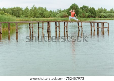 Man doin yoga with beer on pier at lake #752457973
