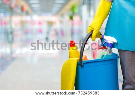 Cleaning lady with a bucket and cleaning products on blurred background. #752459383