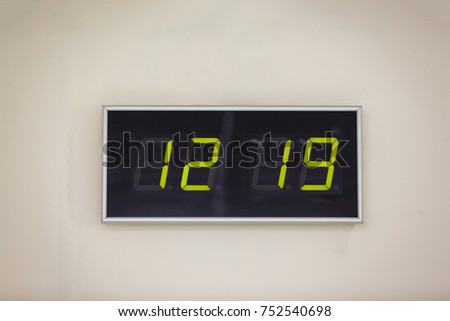 Black digital clock on a white background showing time  #752540698