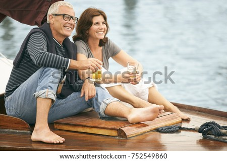 Middle aged couple drinking on boat Royalty-Free Stock Photo #752549860