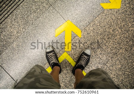 Man standing pointing his shoes to arrow sign #752610961