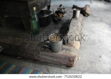 Two metal cups of yak butter tea on logs by a wood fire stove in a travelers tent along the Dolpa trek, Nepal #752650822