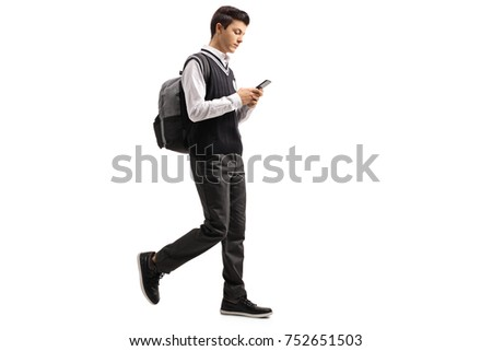 Full length profile shot of a teen student walking and using a phone isolated on white background #752651503