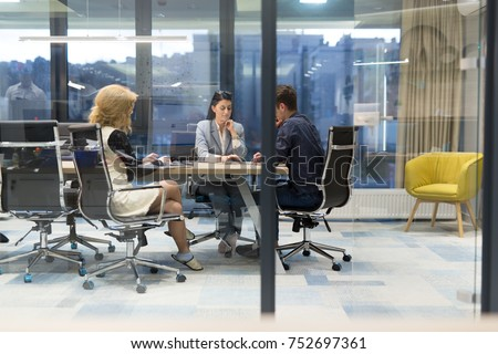 Group of a young business people discussing business plan at modern startup office building #752697361