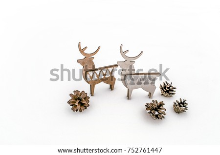 A pair of deer plywood with cones on white snow. Christmas background for presentation of work or text. Copy space. #752761447