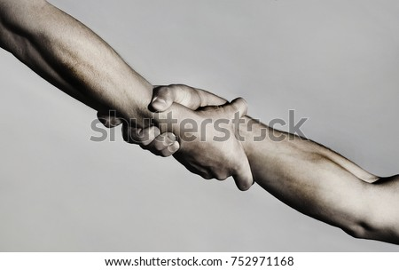 Rescue, helping gesture or hands. Strong hold. Two hands, helping hand of a friend. Handshake, arms, friendship. Friendly handshake, friends greeting, teamwork, friendship. Close-up. Black and white Royalty-Free Stock Photo #752971168