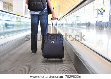 Traveler with a suitcase on the speedwalk #75298336